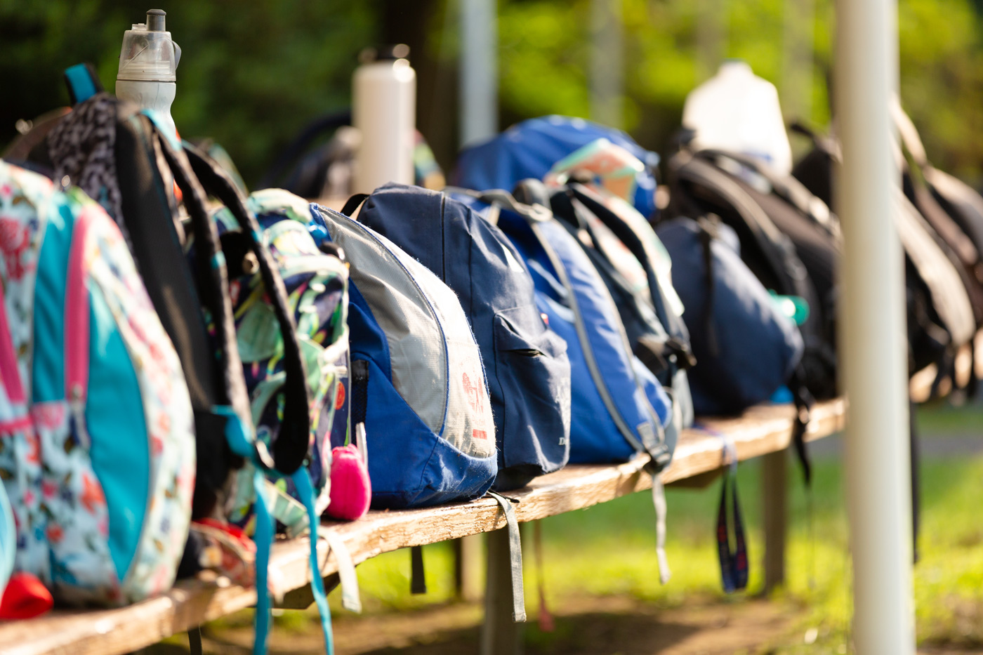 Backpacks lined up on a bench.