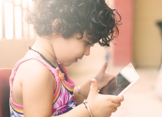 Child playing on a tablet.