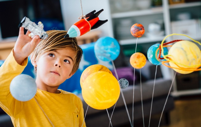 Young boy playing with a toy solar system.